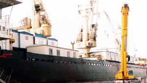 a crane unloading project cargo from a ship. Best example of ocean freight forwarding services