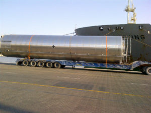 a over sized industrial equipment being unloaded on to a transport company truck from a ship in dubai, international freight forwarders in dubai provide such services.