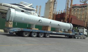 large industrial equipment being unloaded on to a transport company truck from a ship, this is a best example of ocean freight services company in dubai.