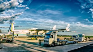 trucks of different companies are waited for there turn to unload cargo in aeroplane
