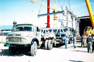 heavy industrial equipment is being loaded by the trained members of the cargo for shipment